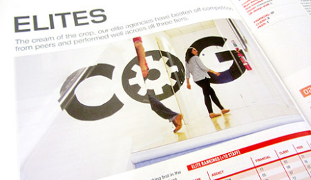 Close crop of a magazine page, featuring an image of a large Cog logo.