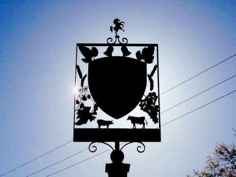 The village sign in Wrotham village with the sun rising behind it.
