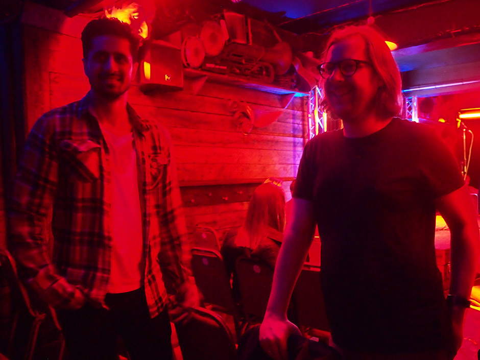 Two young men stand in the red light of a bar
