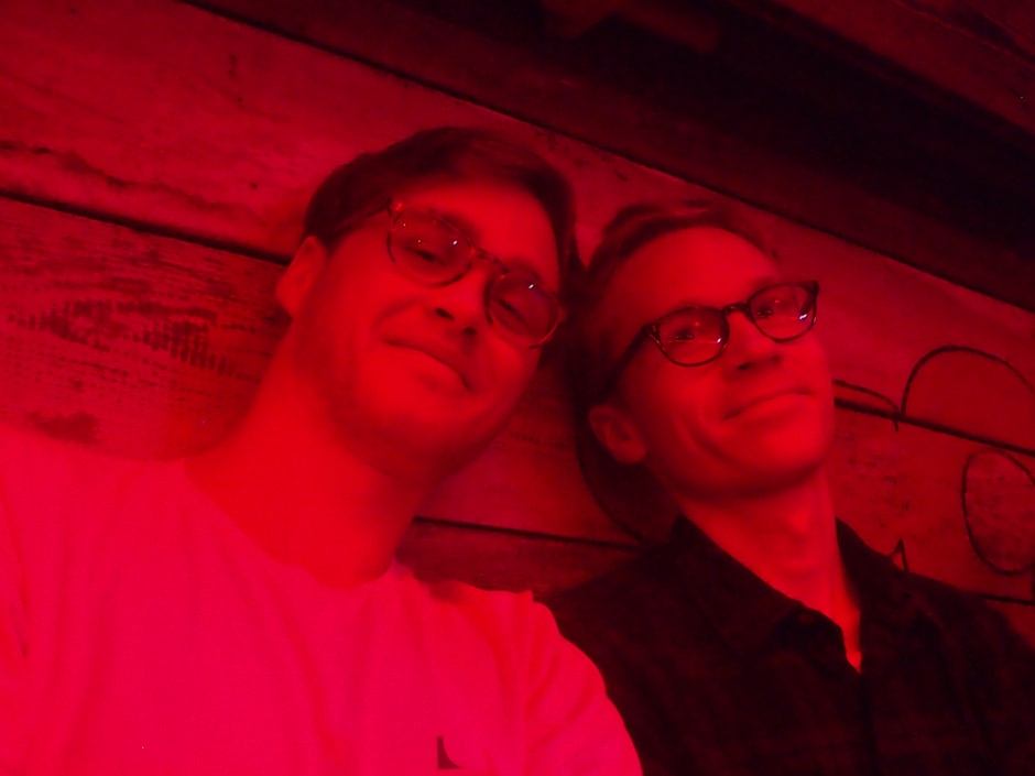 Two young men wearing glasses pose in red light with wooden backdrop