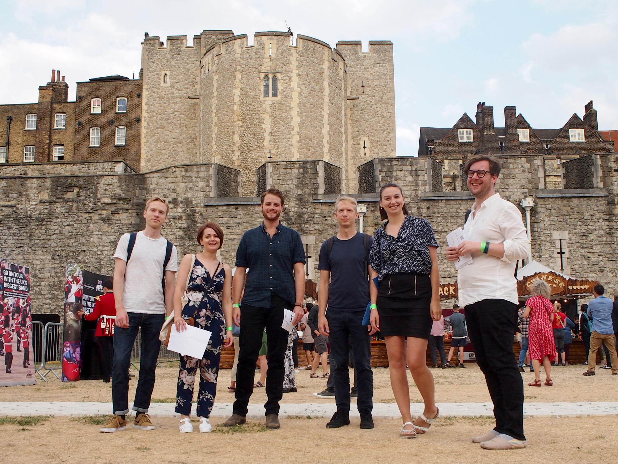 Six casually dressed young adults stand in front of the East Wall of the Tower of London.