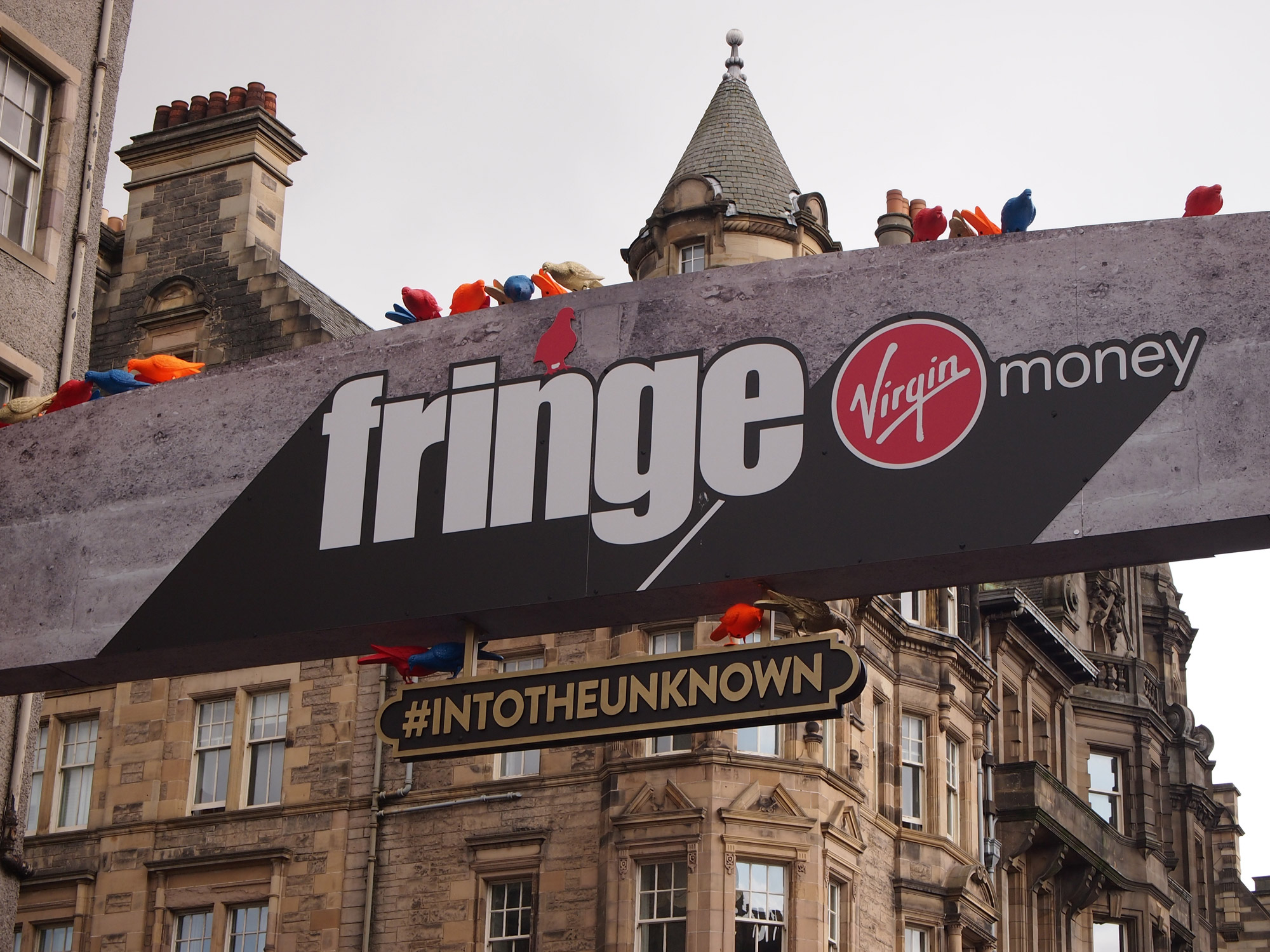 A sign hangs across a road, it is covered in multi-coloured plastic pigeons. The sign reads 'Fringe, into the unknown'. Behind it we see gothic buildings.
