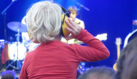 A child with blond hair is sitting on someone's shoulders. The child is looking towards a blue-lit stage. We can see a blured performer playing the guitar. The child is wearing a pair of yellow ear-protecting headphones and holds one side with his right hand.