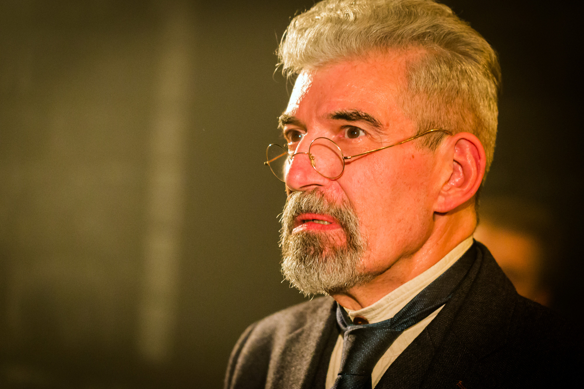 Head and shoulders photo of a middle-aged grey haired man with goatee beard. He wears round, wire-rimmed glasses. His shirt has no collar and is fastened with a stud, with a dark green tie and dark jacket.