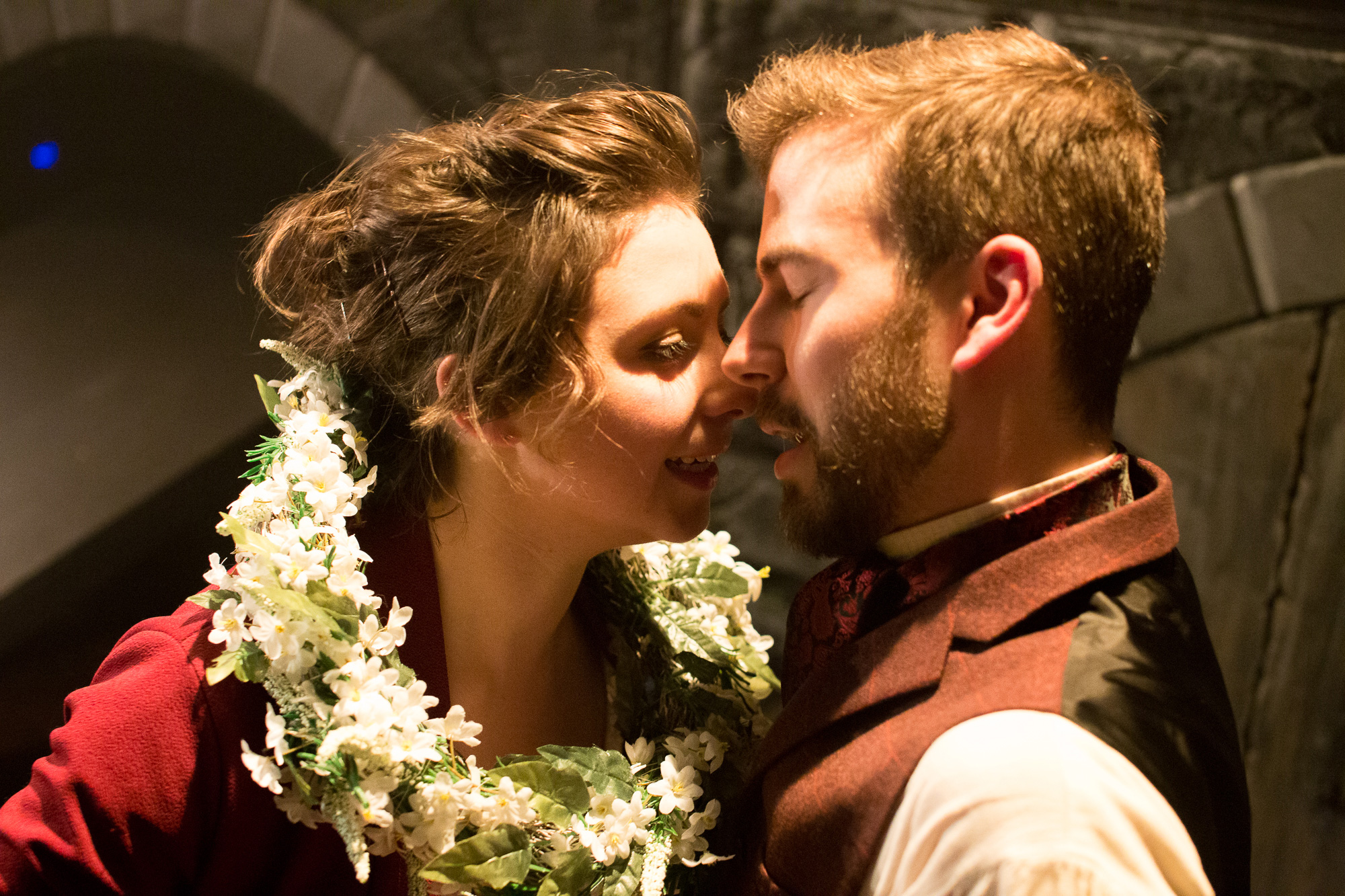A young couple about to kiss, They are dressed in Victorian clothing, she has a flower garland around her neck