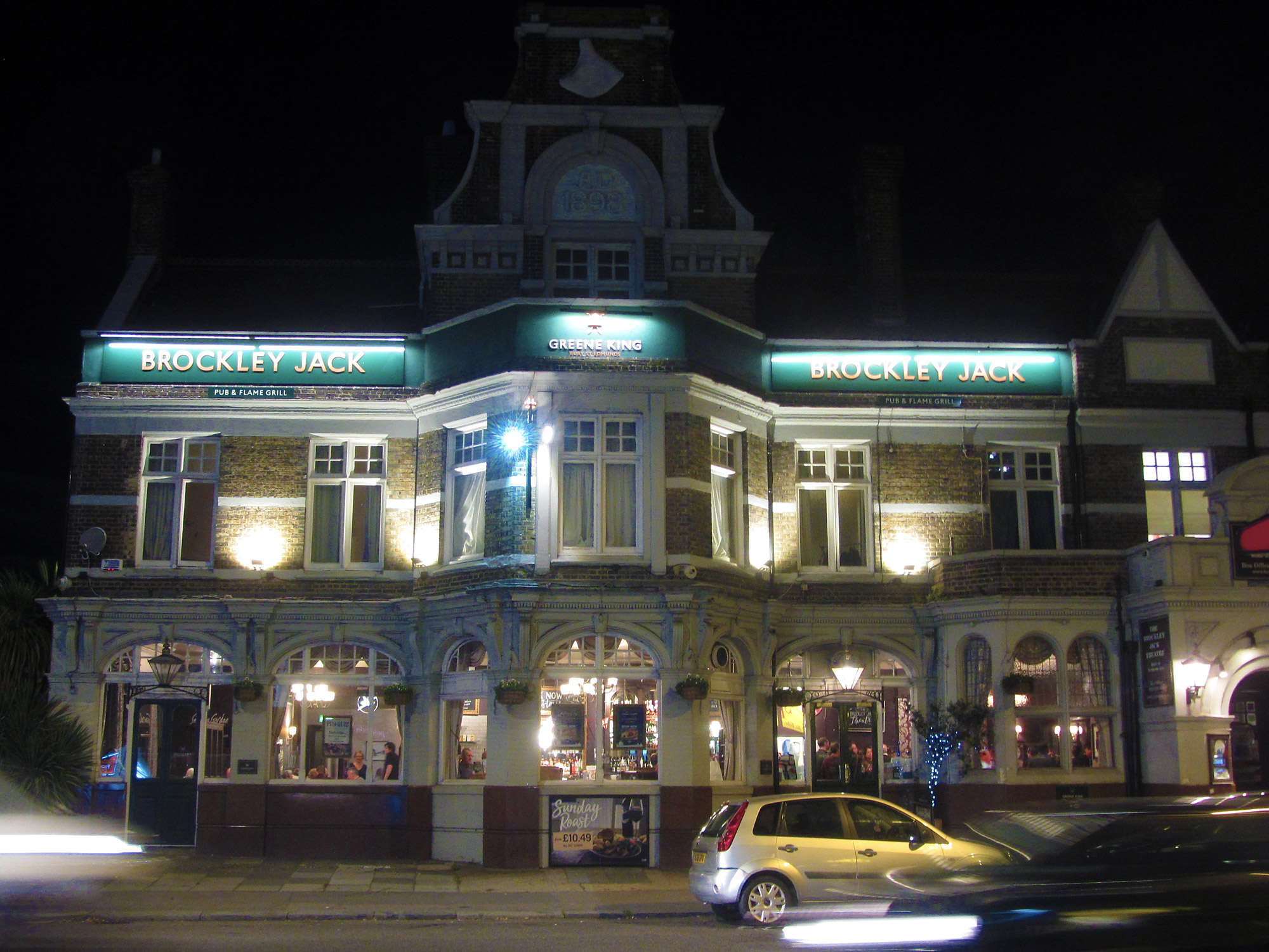 Night time photo of a large pub exterior with cars moving in foreground