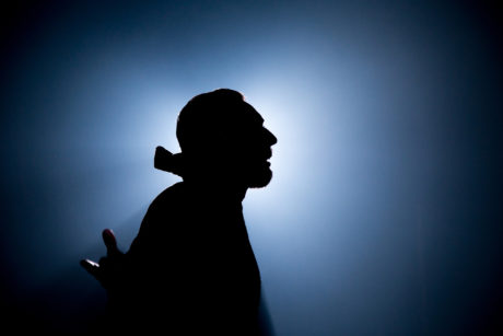 Silhouette of a man in profile. He is wearing what looks like a cloak with a large collar.