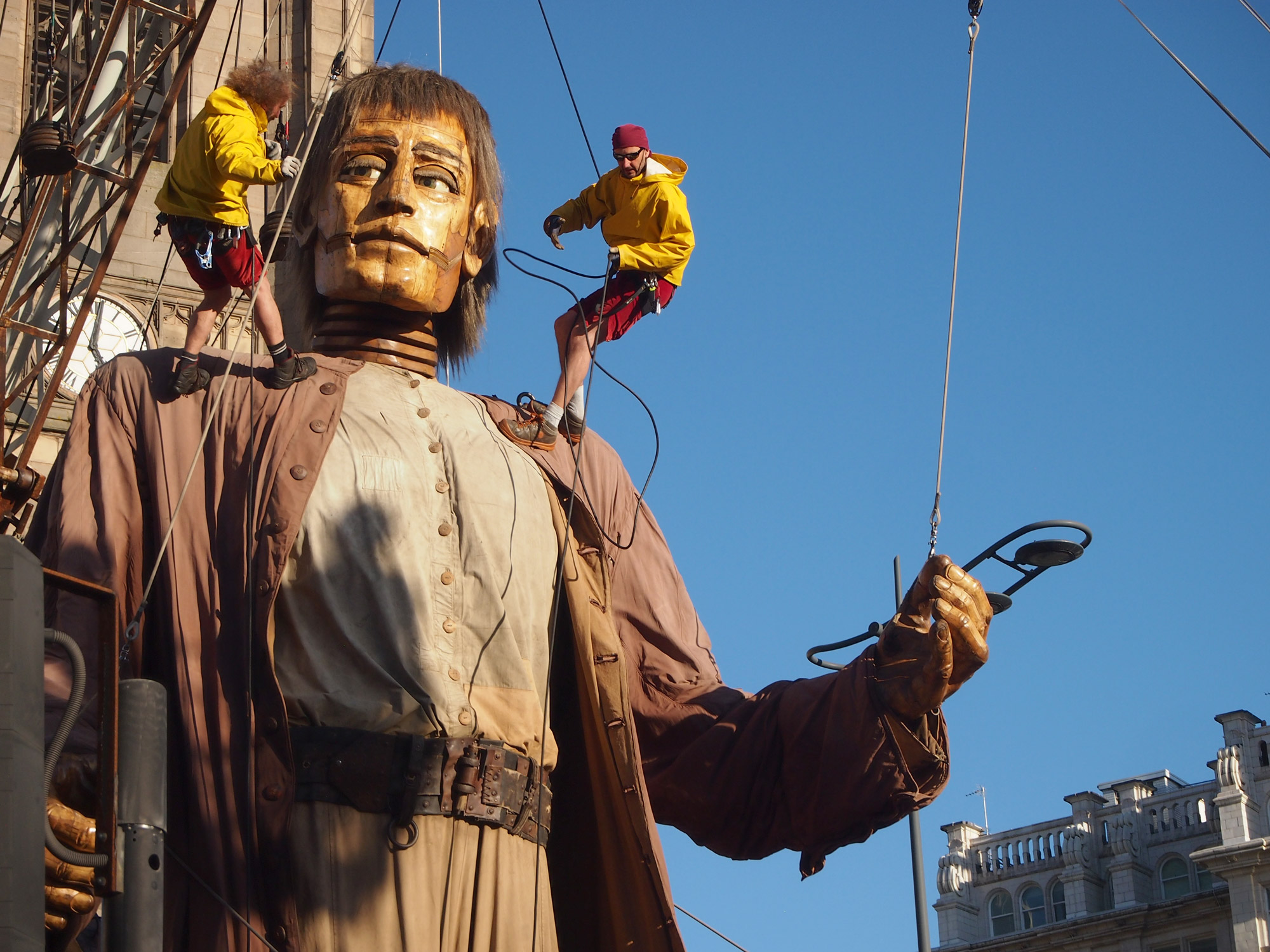 On a giant mannequin, two men hang on ropes. The giant appears to be looking at one of the men.