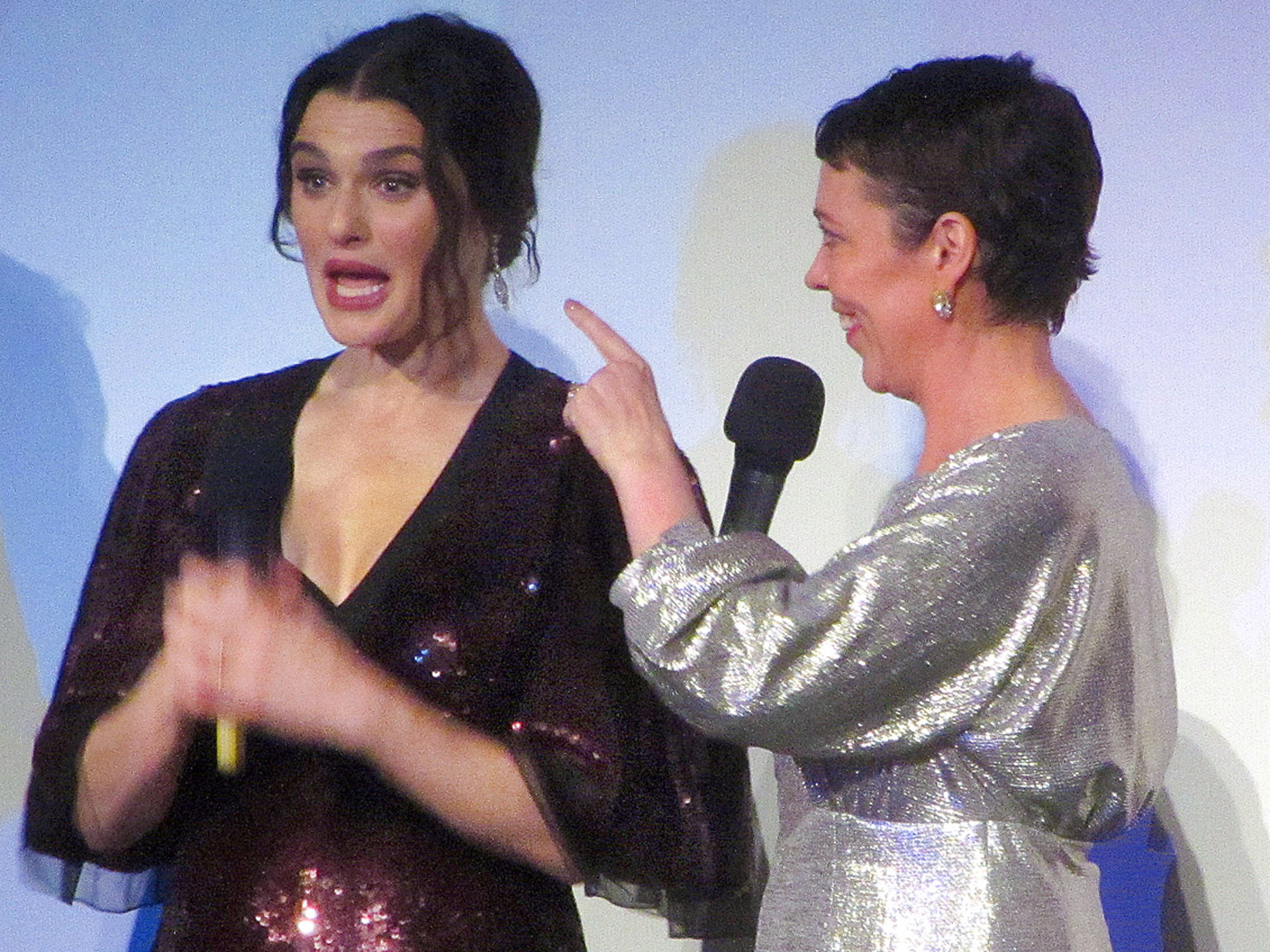 Two woman hold microphones. On the right, the woman in a silver dress points at the woman beside her in a dark red sparkly dress.