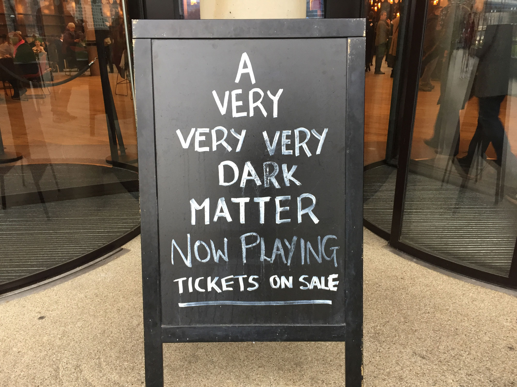 On the ground in front of two revolving glass doors sits a chalk board. On the board is written 'A very very very dark matter now playing...'