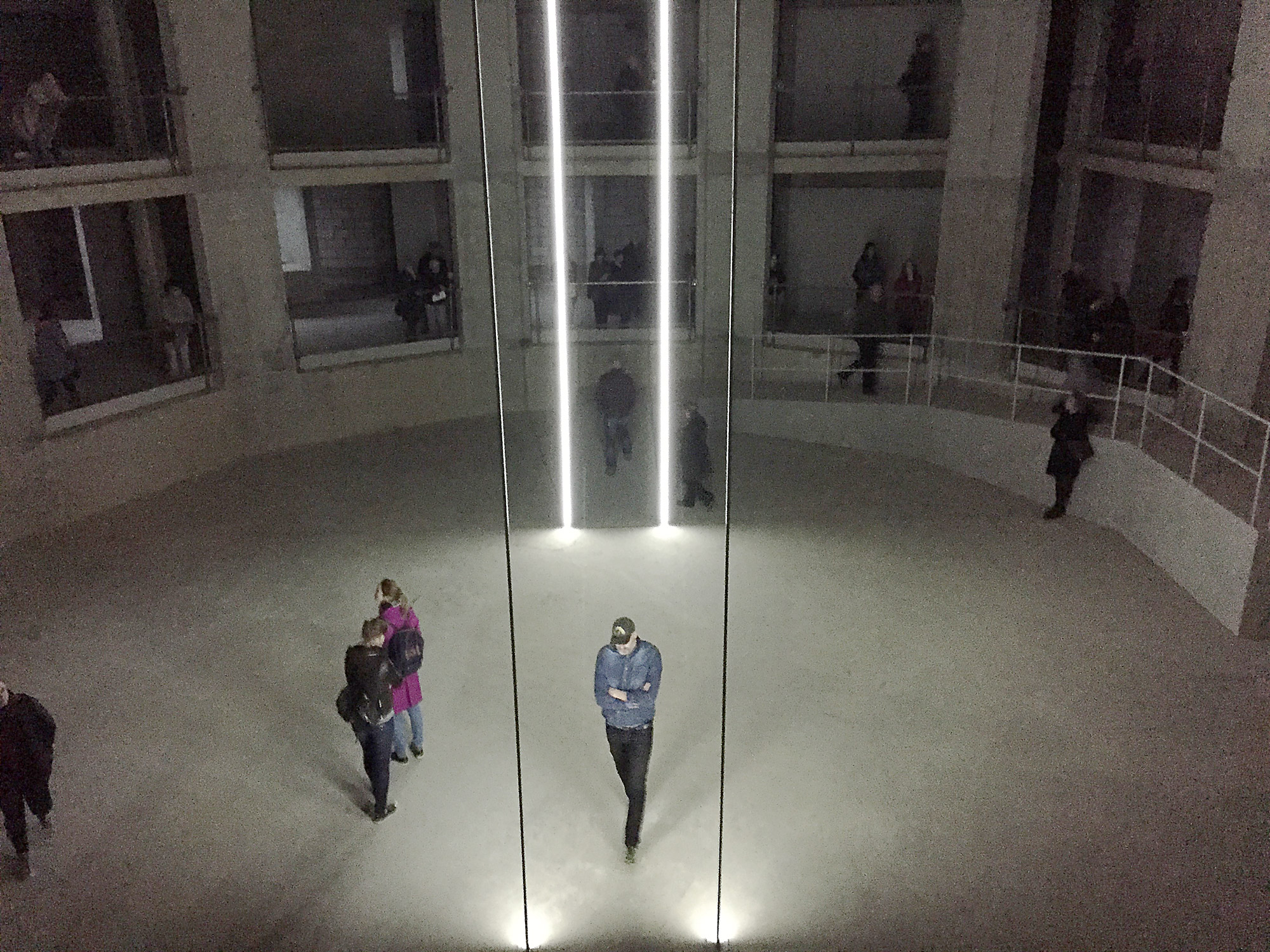 People walk around a large concrete space with apertures on two floors. There are vertical beams of light, cast up from the floor.