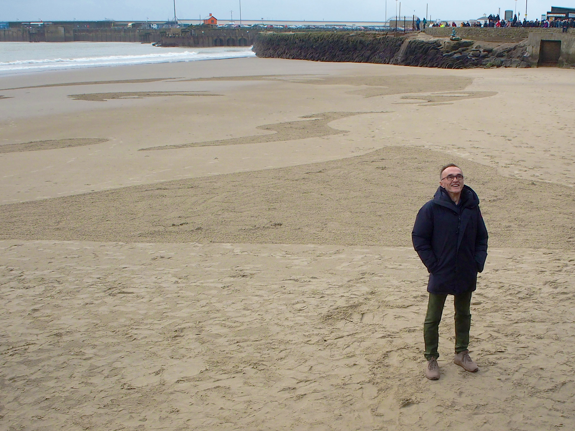 A man stands on an empty, sandy beach. The sand has been raked into a large portrait of a man's face.