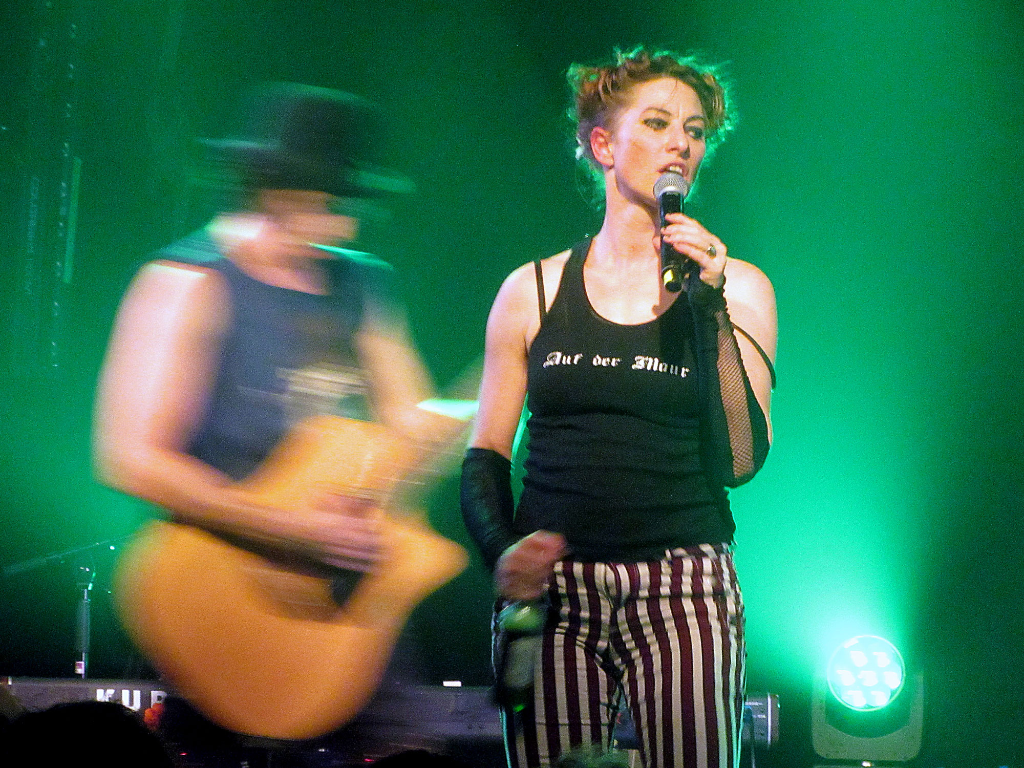 On a green-lit stage, stands a woman dressed in a black vest and stripy trousers. In one hand she holds a microphone, in the other a bottle of beer. Behind her, the blurred figure of a man playing acoustic guitar. He wears a bowler hat.