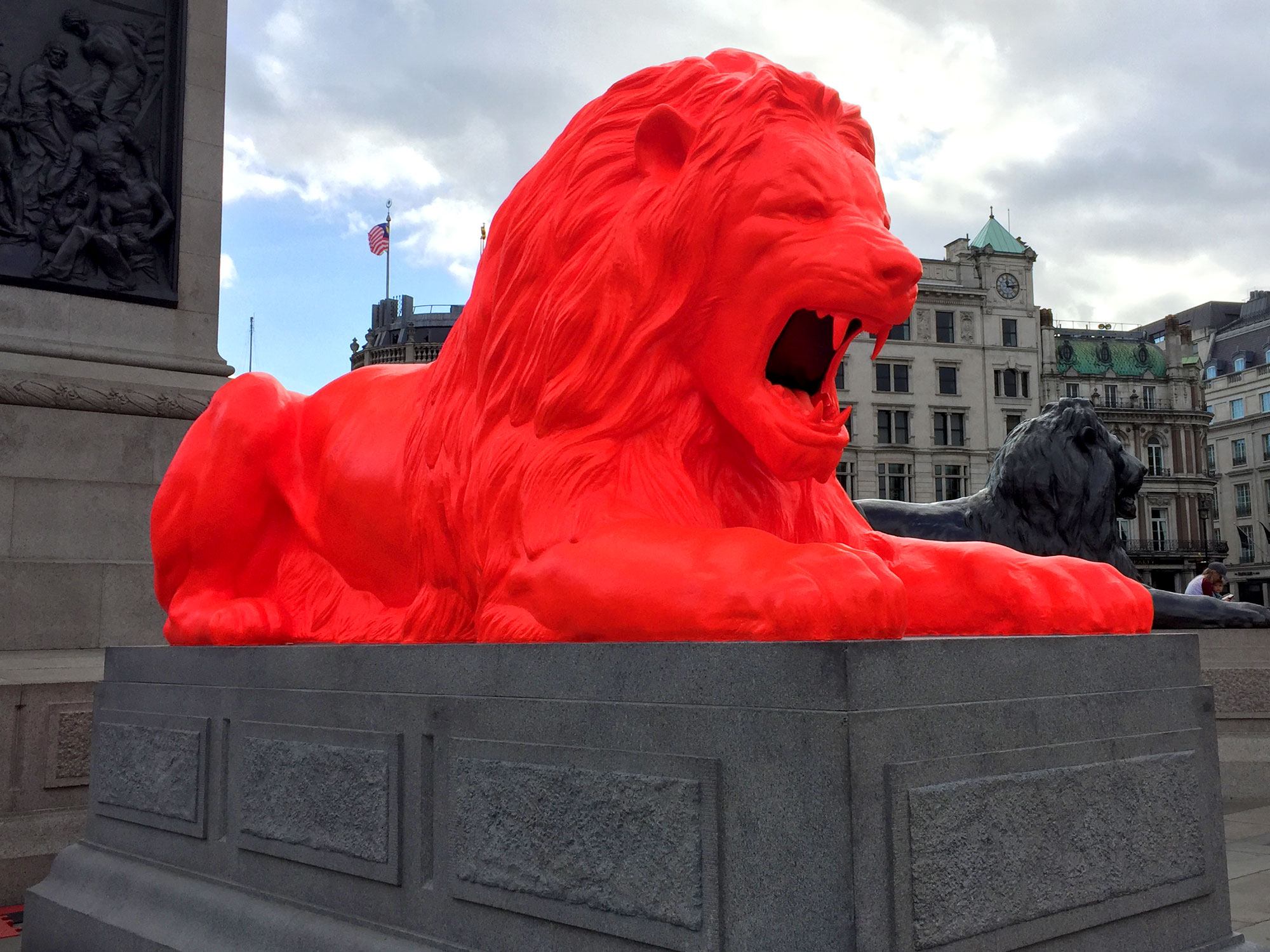On a grey stone plinth sits a reclining line sculpture, painted in fluorescent red paint. Behind it a similar black lion and behind that is a London skyline.