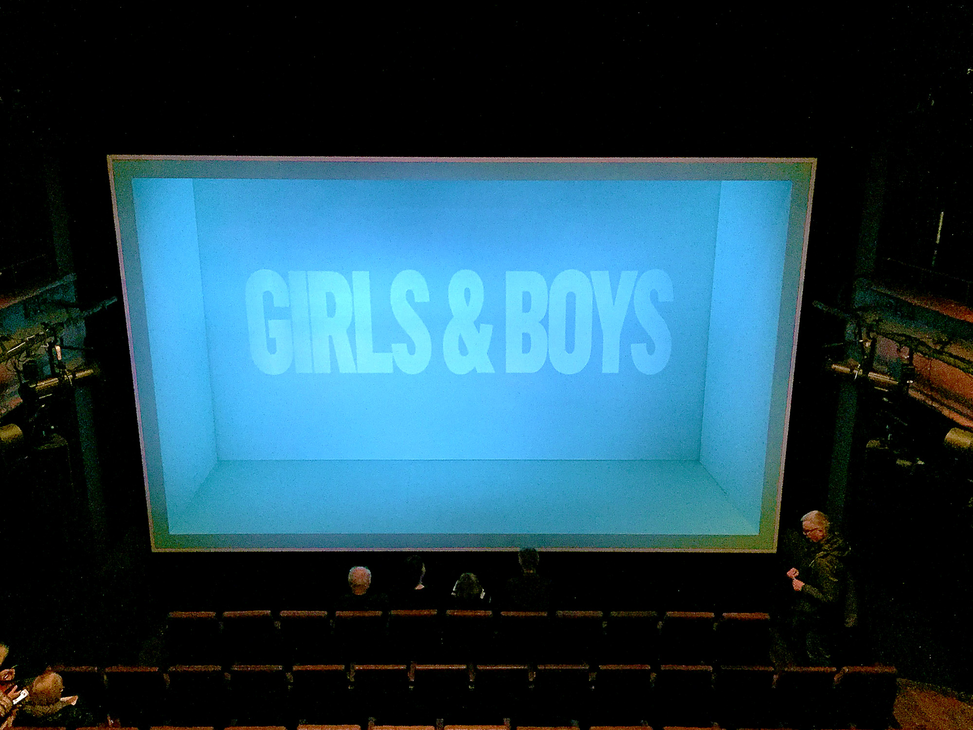 In front of rows of theatre seats, a green-lit box is open on one side towards us. At the rear of the box are the words Girls & Boys.