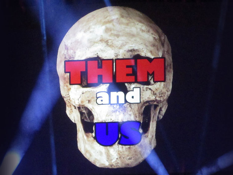 The image of a skull is overlaid with the words Them and Us.