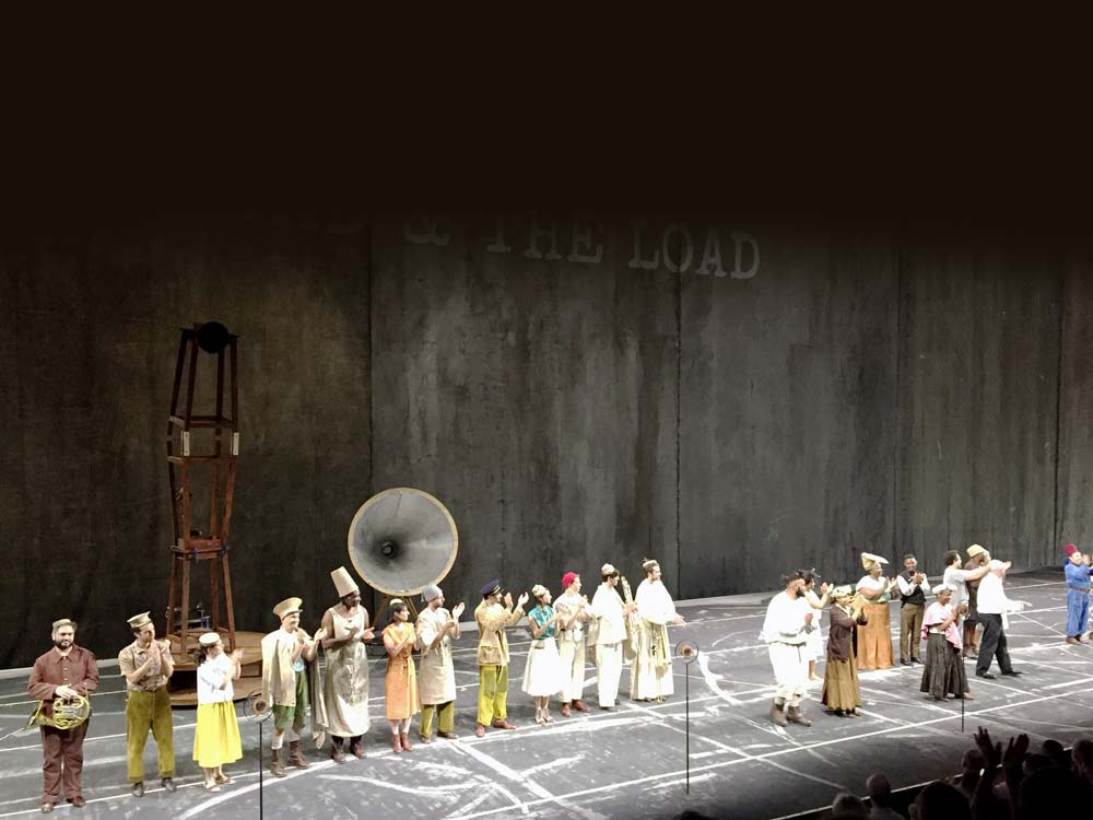 A couple of dozen people, most in traditional African dress, stand on a wide stage against a dark wall backdrop.