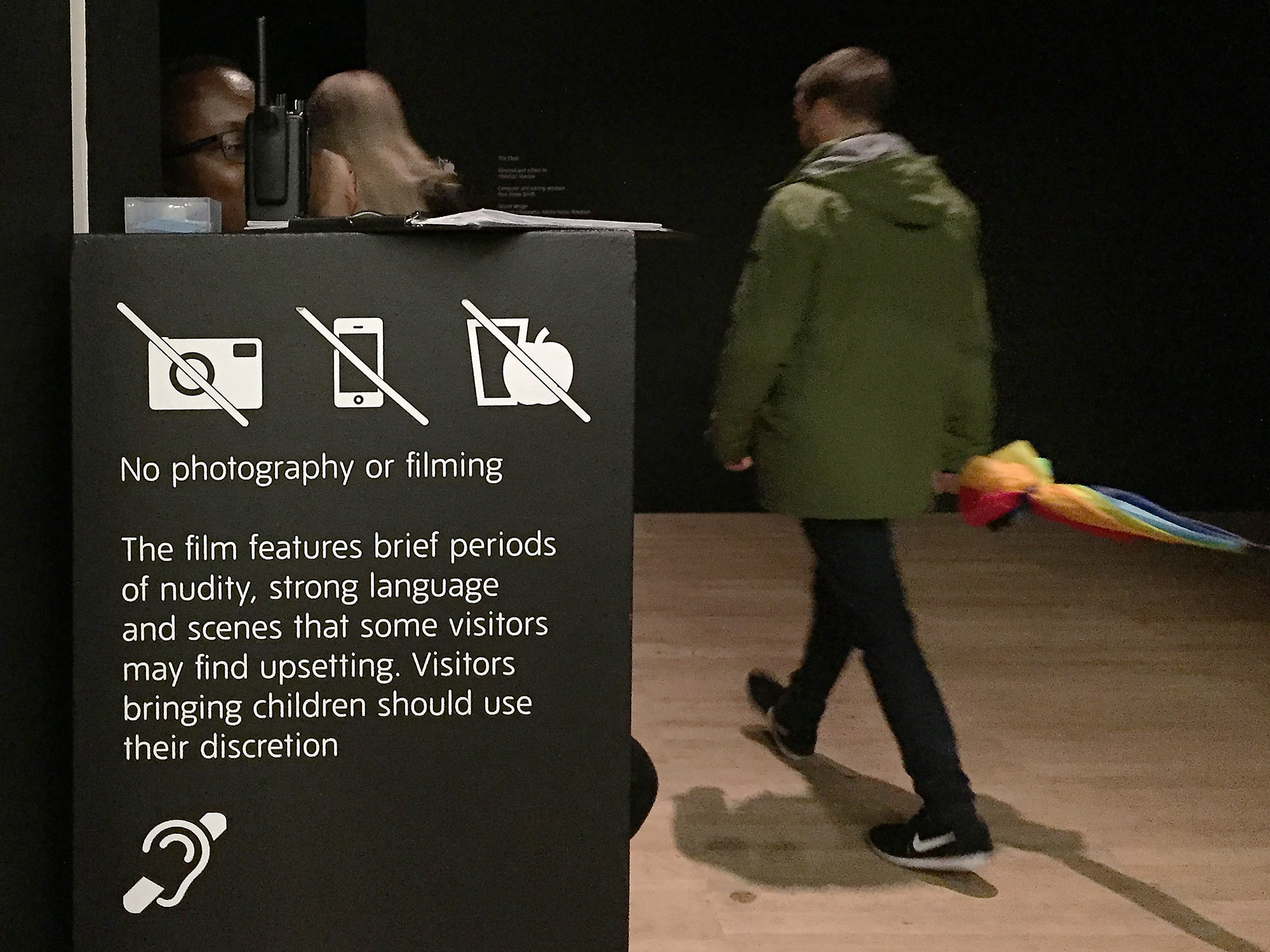 A man walks past a sign that reads 'No photography or filming...'