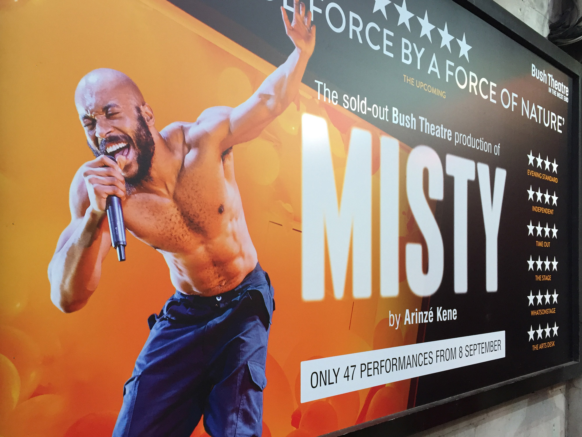 On an orange background, a landscape poster shows a muscly man, with bald head and beard, singing into a microphone. Beside him is the word MISTY...