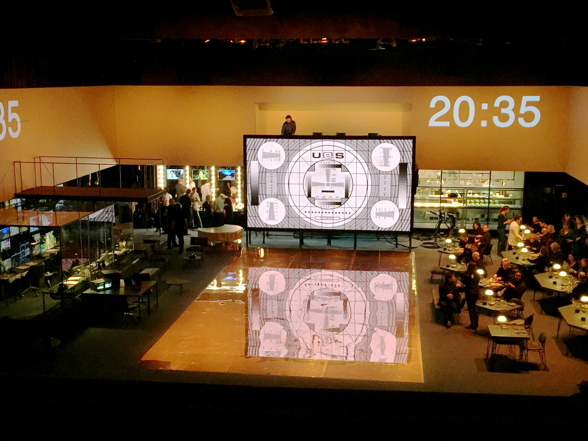 A large, open stage. To the right are several tables with people aorund them. To the rear a large screen shows a test-card, next to it a projected digital clock reads 20:35.
