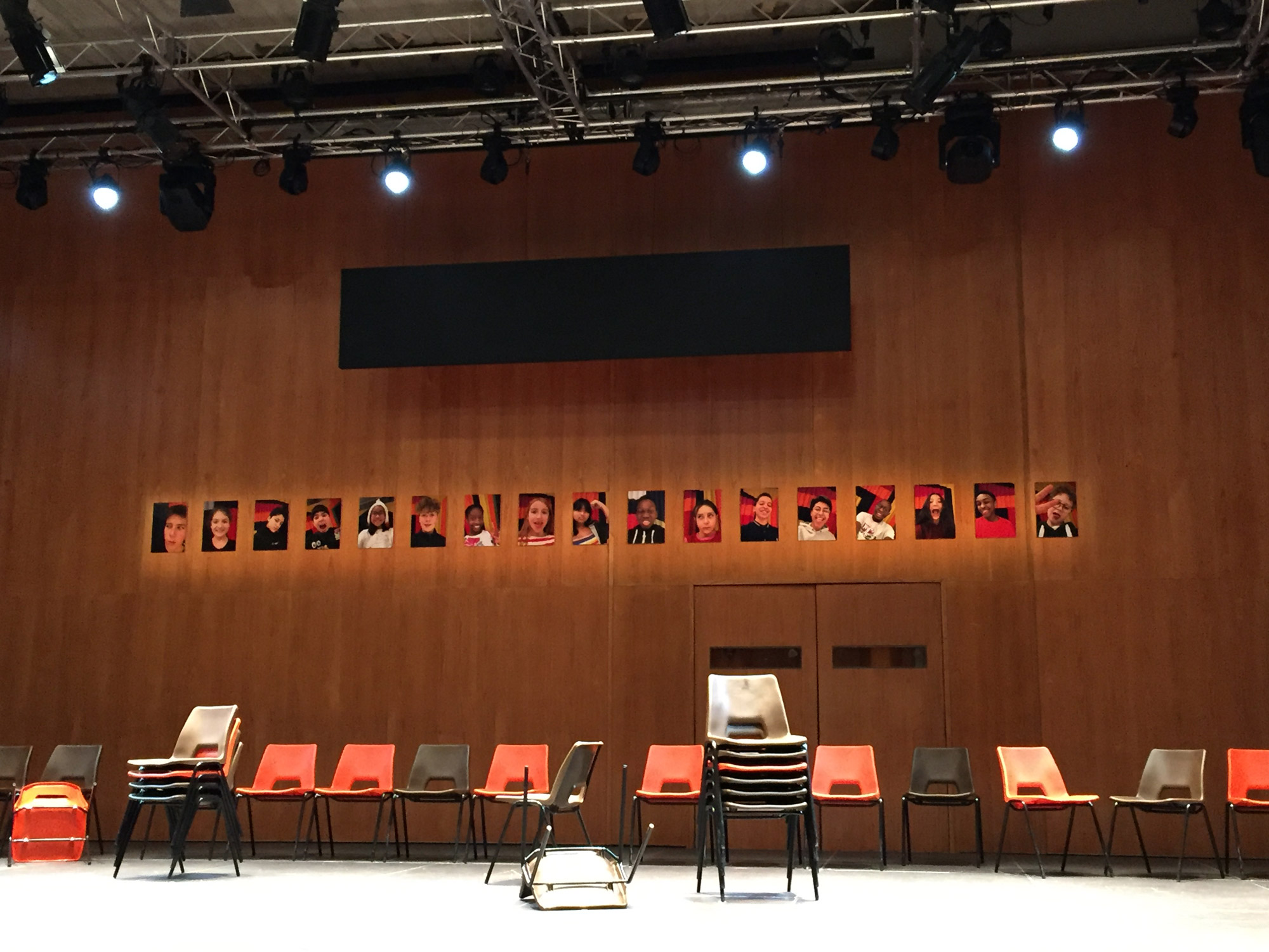 Dozens of plastic chairs are stacked and scattered on an otherwise empty stage. Behind them a wooden backdrop has 17 small photographs of children stuck in a row