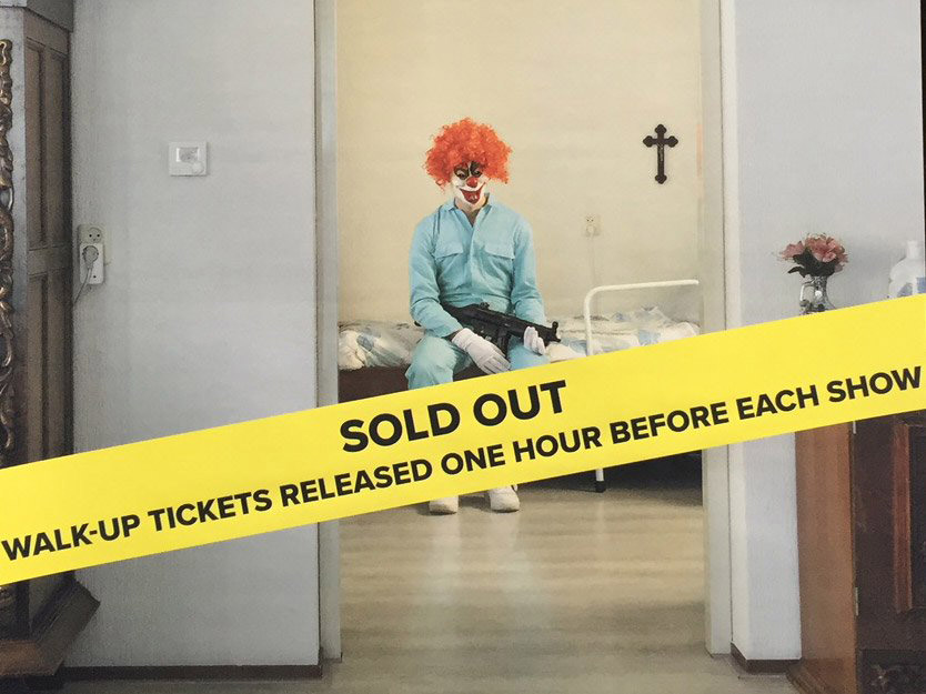 Through a doorway we glimpse a man dressed in a blue boiler-suit, a clown-mask and red wig. He is sitting on a bed holding a machine-gun. Across the whole image is a yellow strip reading Sold Out...