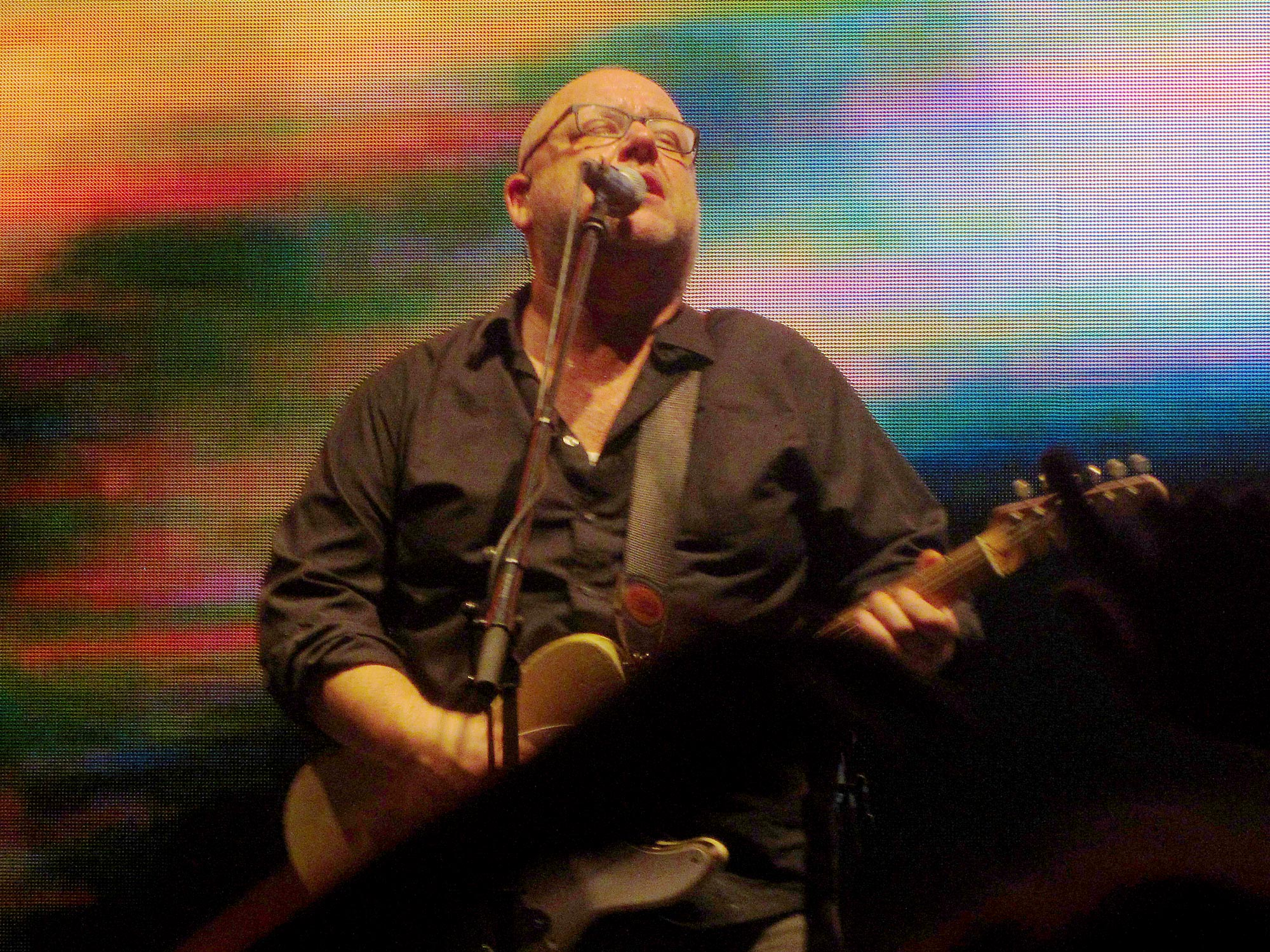 A bald man in glasses sings into a microphone whilst playing guitar. Behind him is a multicolour digital screen.