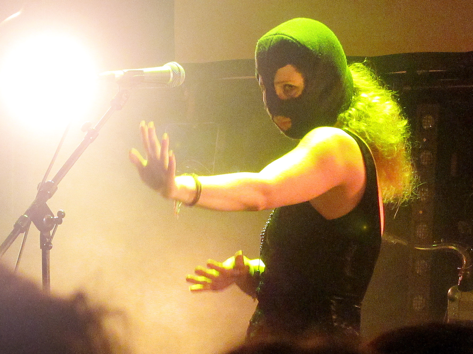 A woman dressed in a sleeveless top is dancing on a misty stage, She is wearing a green balaclava, her hair billowing out of the back.