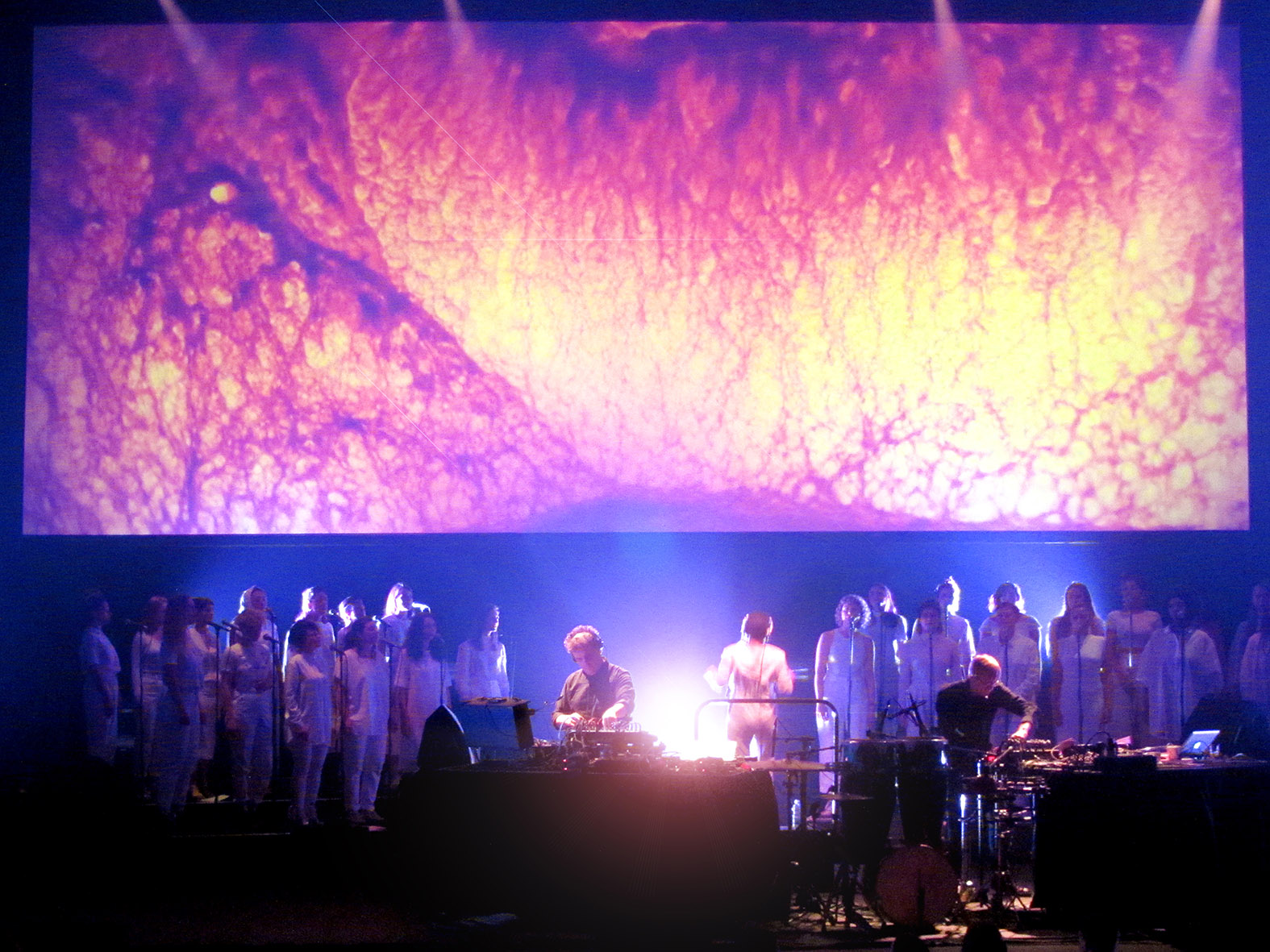 Two DJs perform in front of an all-female choir. Behind them is an abstract image projection.