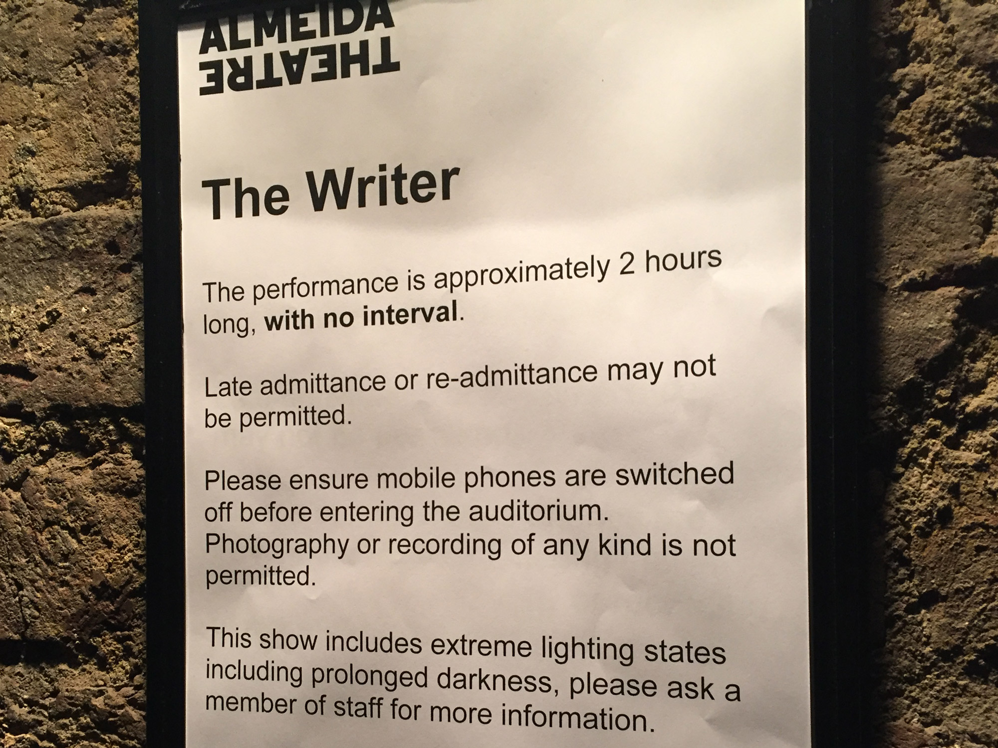 A sign, mounted on a brick wall. The sign read 'The Writer' and has a notifications about the event.