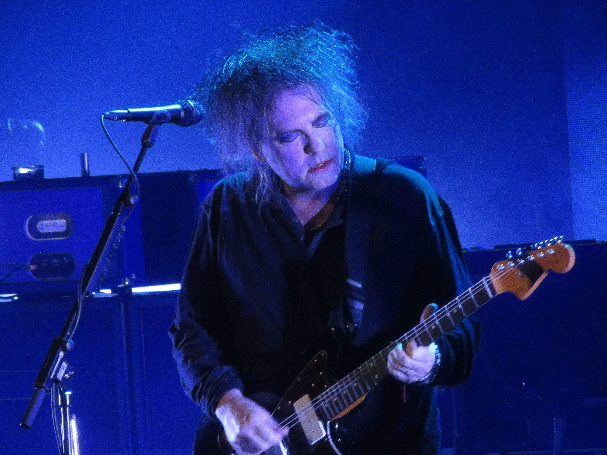 On a blue-lit stage, behind a microphone, a man with unkempt dark hair plays guitar. He is wearing make-up.
