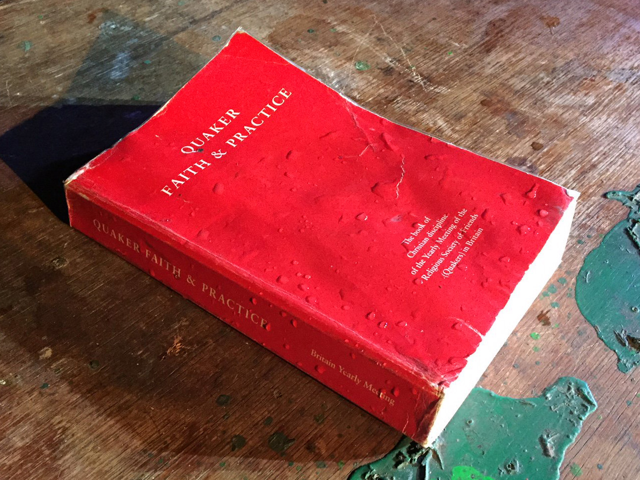 A water-soaked book, with a red cover, sits on a paint-splattered wooden surface.