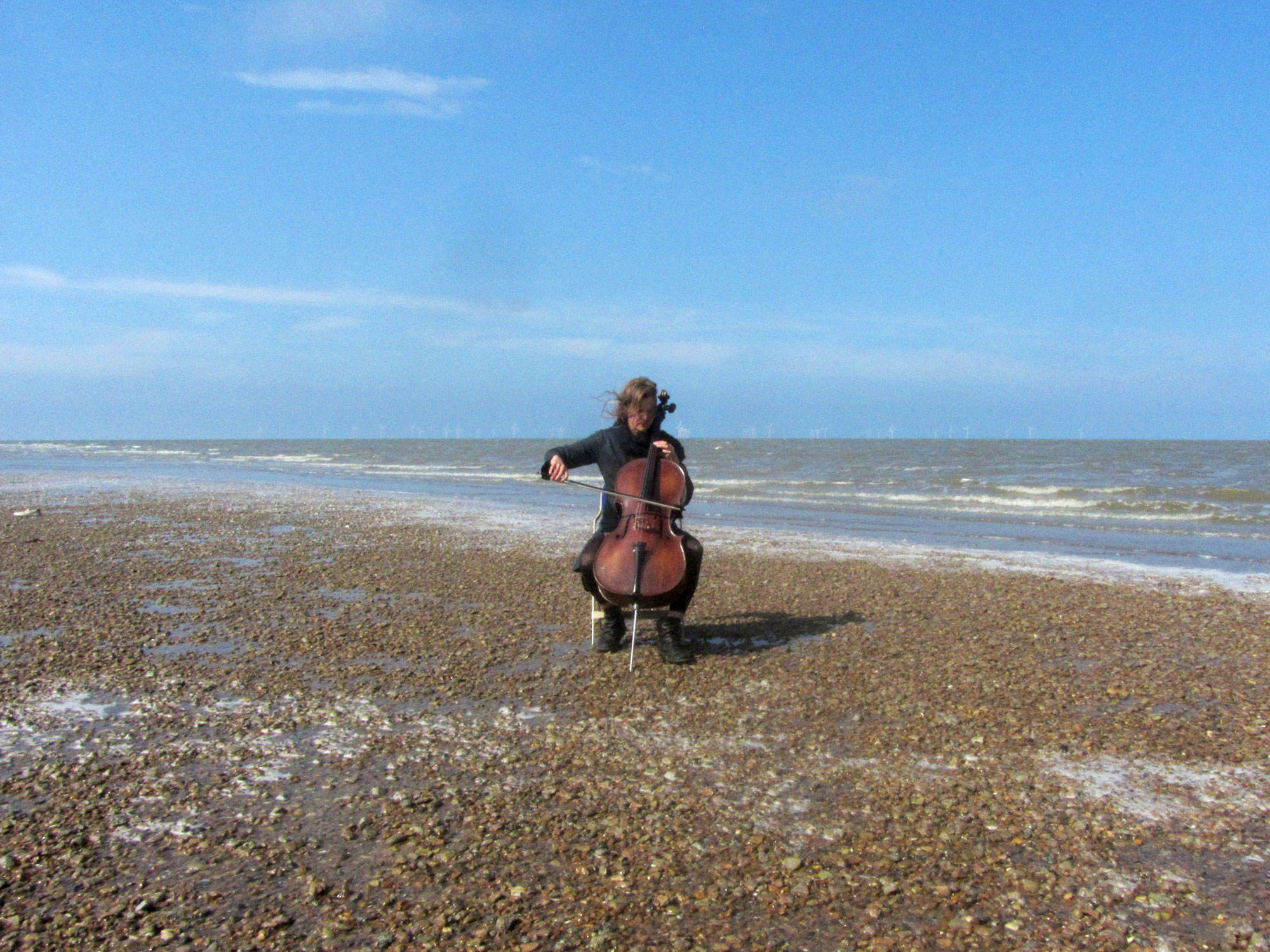 Under a blue sky, on a shingle beach, a woman plays a cello. Behind her we can see the sea.