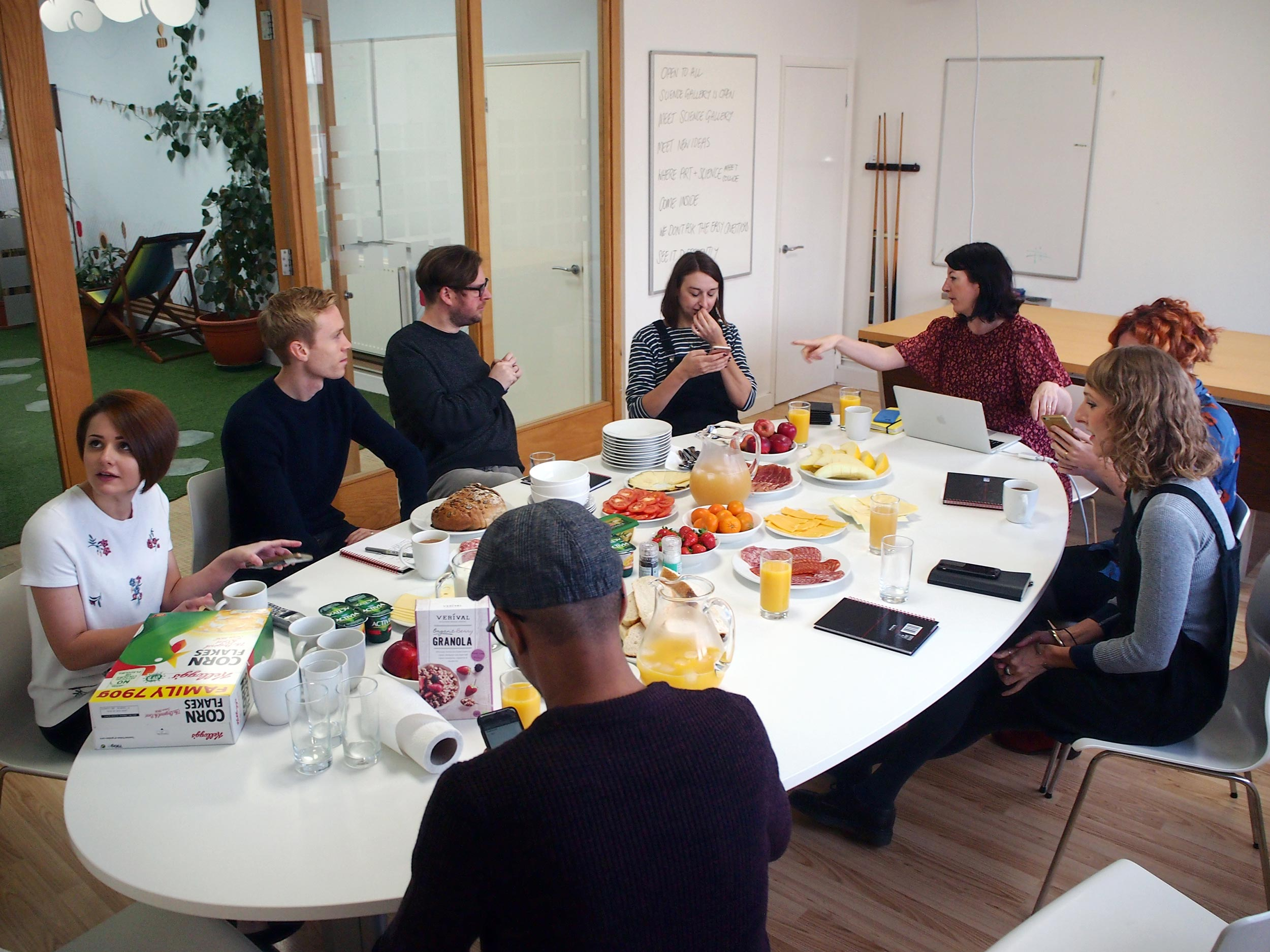 Eight people sitting around a white oval table, filled with fruit and other breakfast food