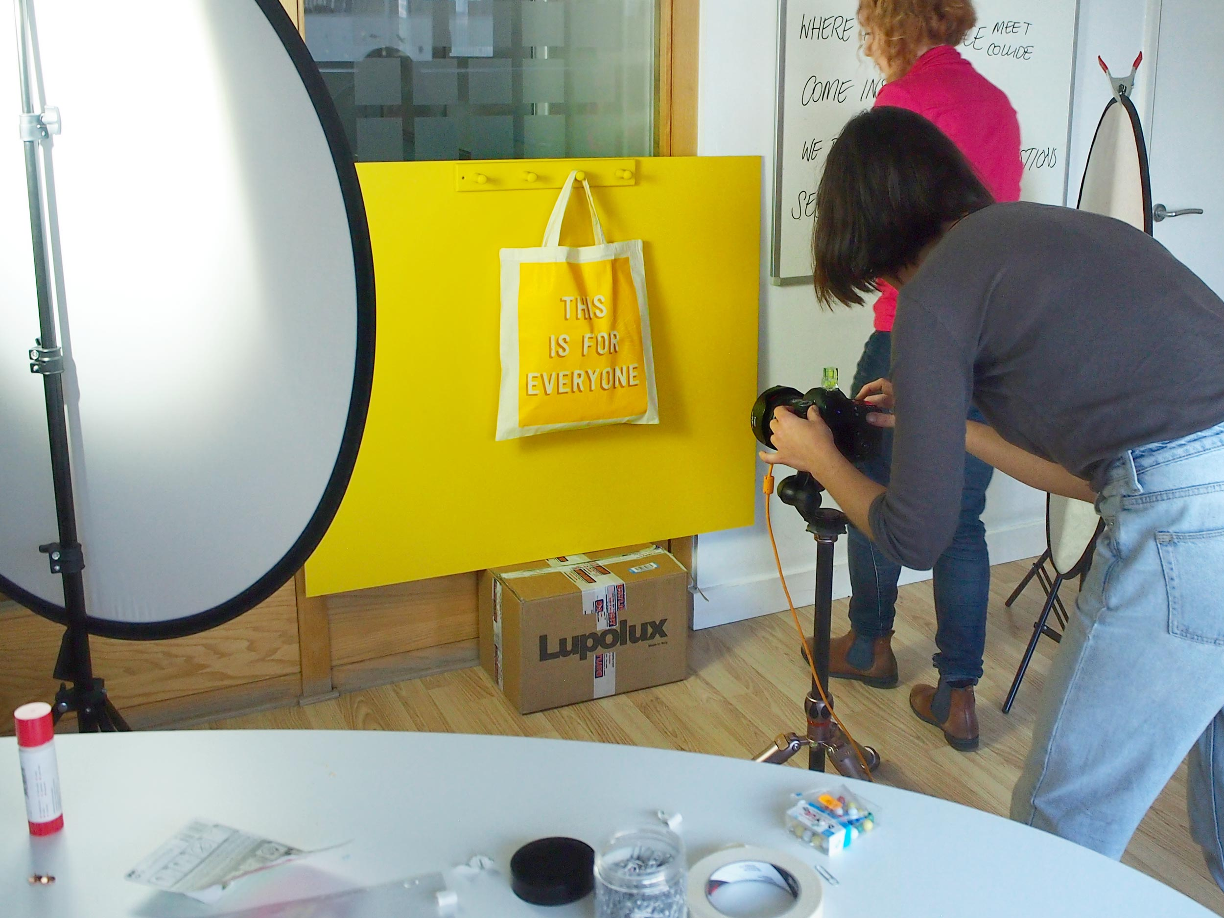 A studio set up with a photographer, shooting an image of a yellow bag on a yellow backing board