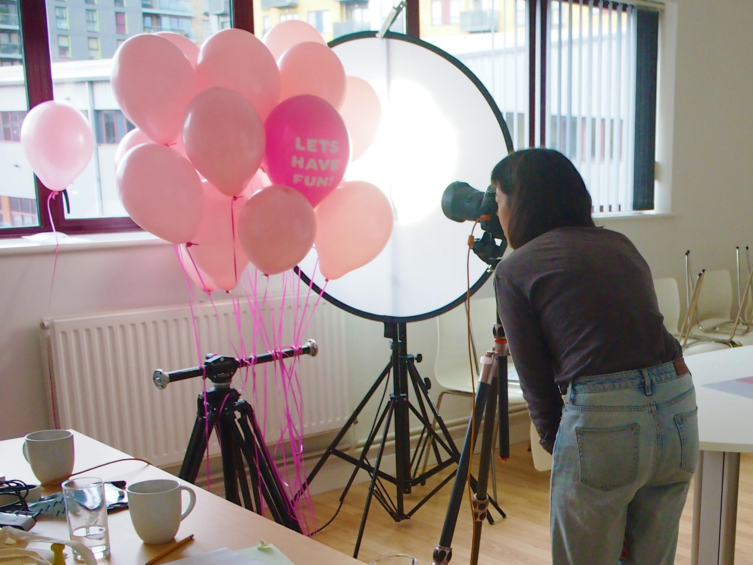 A photographer shoots pink balloons against the light of a window.