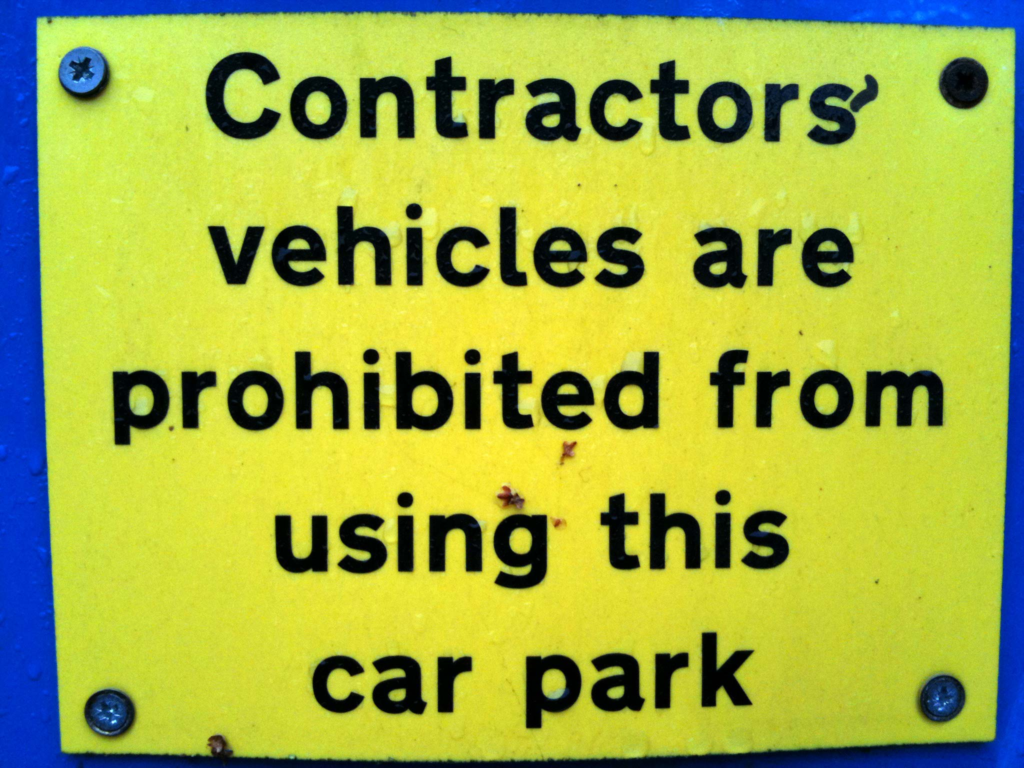 Yellow sign with black type that starts: Contractors vehicles are prohibited. In black pen, an apostrophe has been added after the s of Contractors.