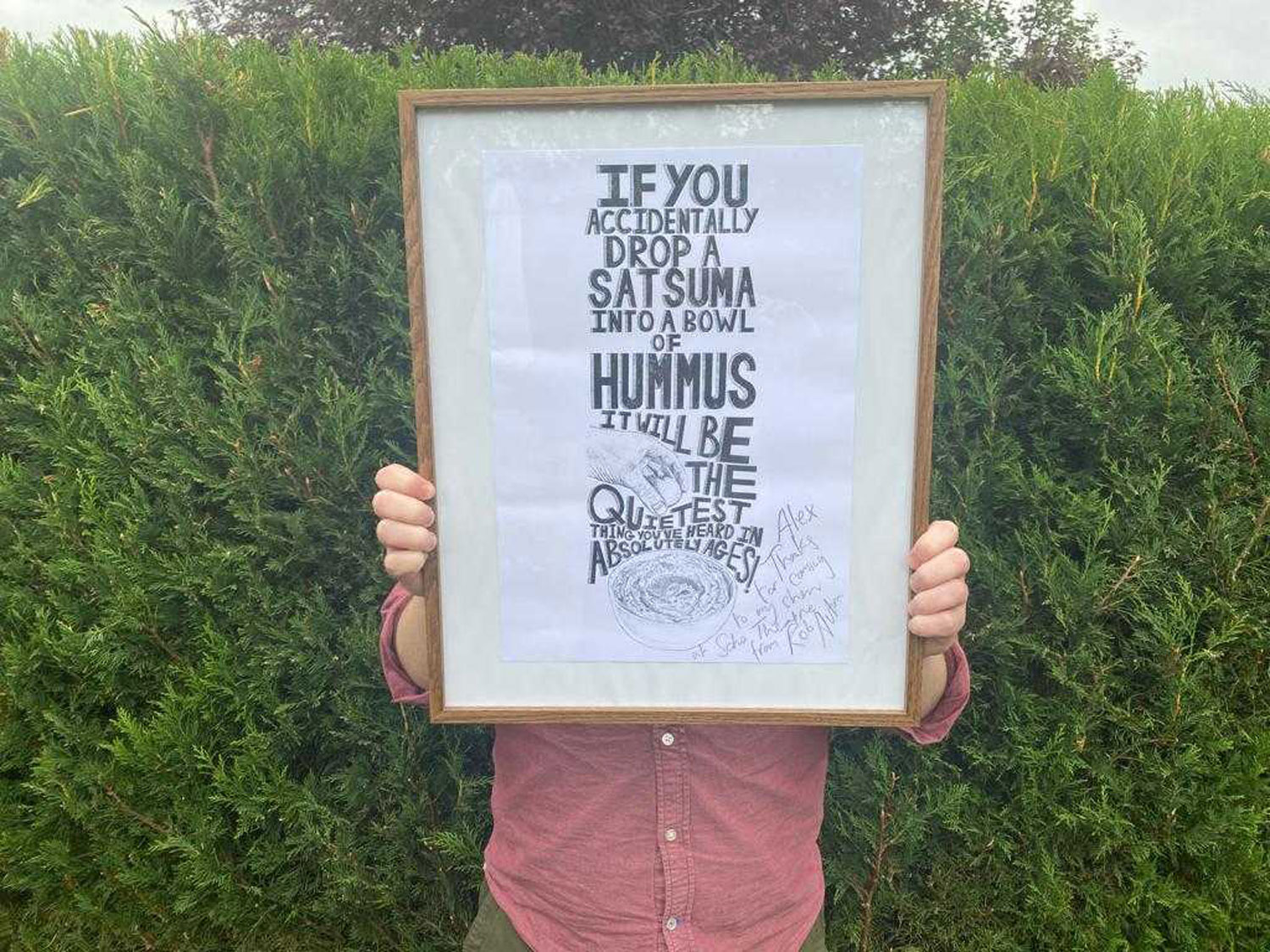 Alex from Cog holds up an illustrated print in a wooden frame signed by the artist Rob Auton
