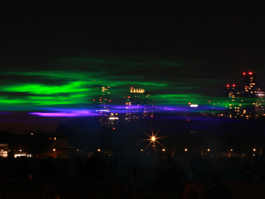 Green and purple lights recreate the Northern Lights in Greenwich in the dark, with the lights of Canary Wharf behind