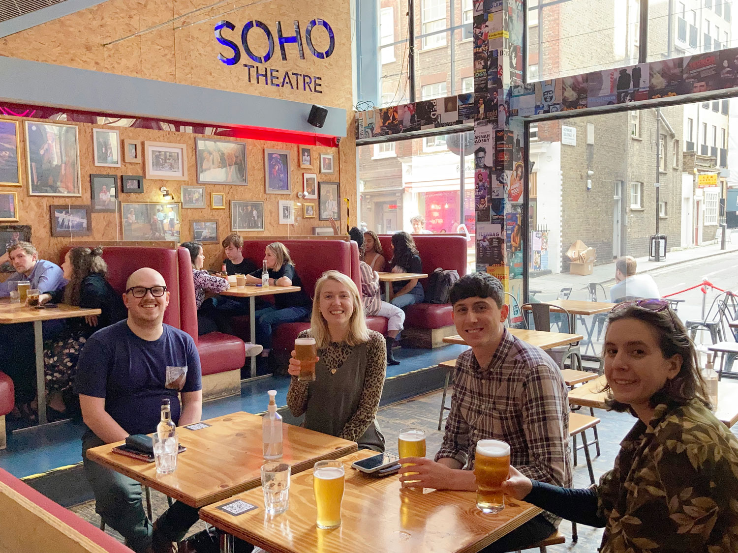 Four members of the Cog team sit at a table smiling and holding drinks at the Soho Theatre bar