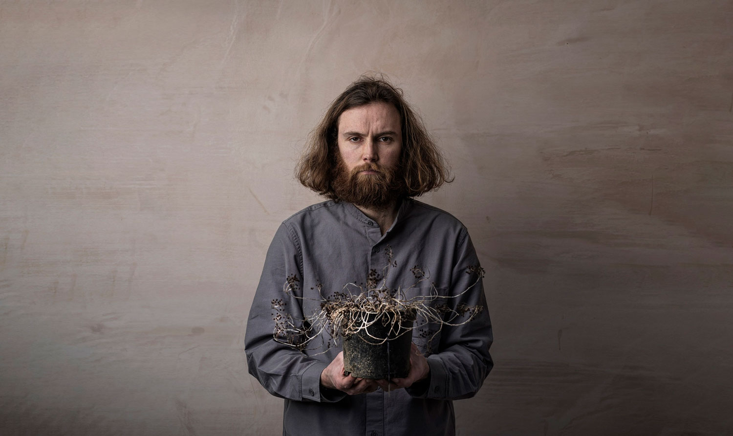 An image of the comedian Rob Auton looking gloomy holding a dead plant depicting the passage of time
